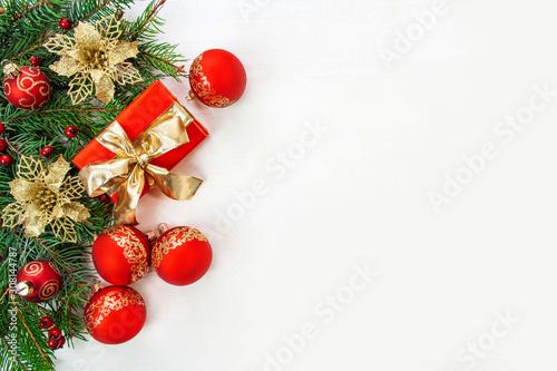 Vászonkép Bożonarodzeniowe tło - gałęzie świerku, prezenty i czerwone i złote ozdoby na bi