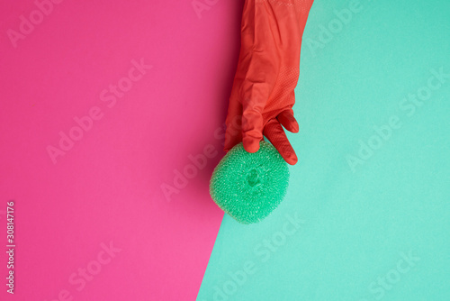 Photo  hand in an orange glove holds a kitchen green sponge