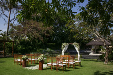 Beautiful Romantic Outdoor Wedding Setup In Tropical Garden, Wooden Chairs And Simple Gazebo Decorated With White Flowers