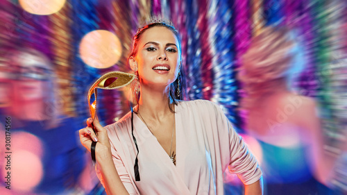 Fototapeta  woman on party with mask dancing in night club