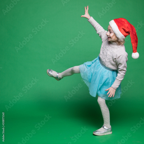 Happy little girl in Santa Claus hat jumping Canvas-taulu