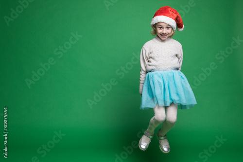Valokuvatapetti Happy little girl in Santa Claus hat jumping