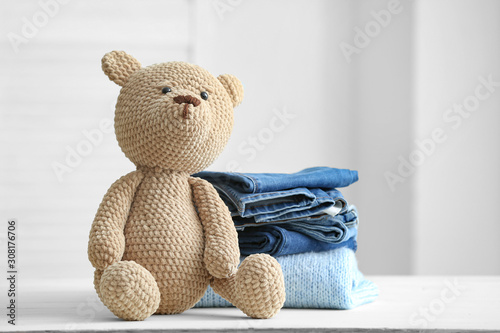 Slika na platnu Stack of clean kid clothes with toy on table in room