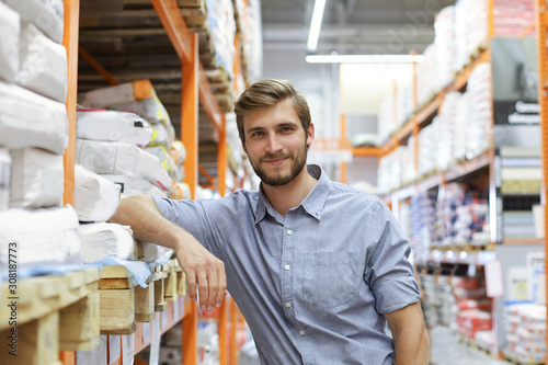 Fotografiet portrait of a smiling young warehouse worker working in a cash and carry wholesale store