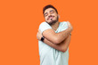 Leinwandbild Motiv I love myself! Portrait of egoistic brunette man with beard in white t-shirt standing with closed eyes, embracing himself and smiling form pleasure and proud. indoor, isolated on orange background