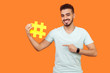 canvas print picture - This is internet trend. Portrait of positive brunette man with beard in white t-shirt smiling and pointing at big hashtag sign, sharing viral content. indoor studio shot isolated on orange background