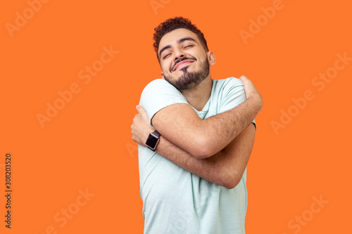 Платно I love myself! Portrait of egoistic brunette man with beard in white t-shirt standing with closed eyes, embracing himself and smiling form pleasure and proud