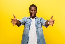 Free Hugs, Come Into My Arms. Portrait Of Friendly Kind Man In Denim Shirt Stretching Hands To Camera And Smiling Broadly, Going To Embrace, Share Love. Studio Shot Isolated On Yellow Background