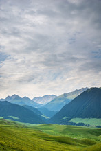 Mountain Nature Cloudscape With Grassy Green Meadow