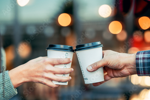 Obraz a couple is toasting with paper cup and drink coffee - fototapety do salonu