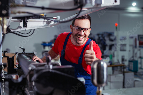 Industrial worker thumb up in factory. Canvas Print