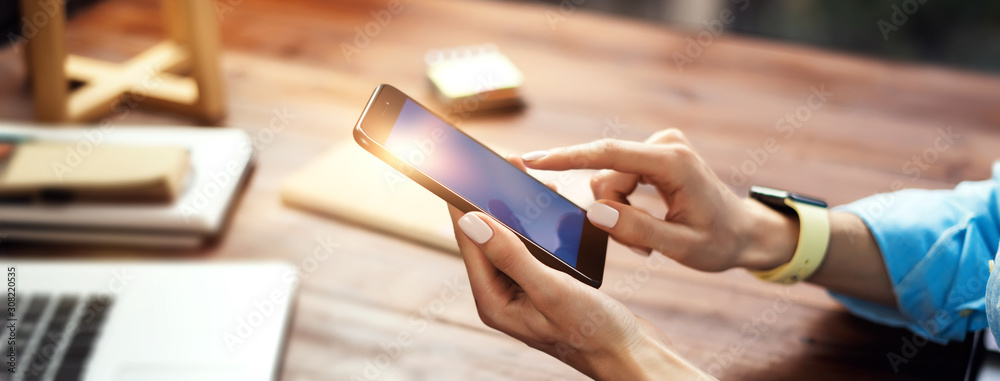 Fototapeta Woman pointing on smartphone screen, chatting in social networks, meeting website, searching internet, sending sms, using text messenger or online banking. Close up of female hands