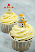Cupcakes With Butter Cream Decorated With Snowman Figurine On Grey Background