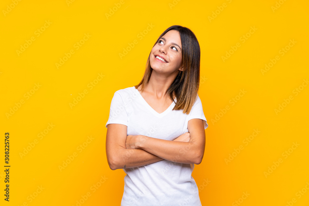 Fototapeta Young woman over isolated yellow background looking up while smiling