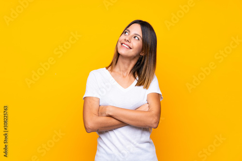 Obraz Young woman over isolated yellow background looking up while smiling - fototapety do salonu