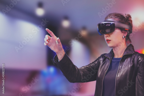 Photo Portrait of young Caucasian woman using augmented and virtual reality with holographic hololens glasses
