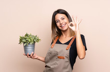 Young Woman Holding A Plant Sh...