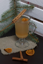 Orange Drink In A Glass Goblet. A Slice Of Dried Orange Floats In It. Nearby Are Cinnamon Sticks And Dried Oranges.