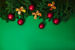 Natural green fir branches flat lay with red christmas balls and golden baws. Christmas card with copy space.