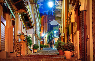 Fototapeta Uliczki Bellagio village at lake Como near Milan Italy, region Lombardy. Famous street with paving stones stairs and cosy restaurants during sunrise with glowing lanterns and green plants on old houses walls.