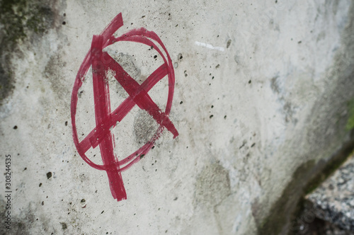 Closeup of red anarchy symbol painted on cement wall in the street Canvas Print