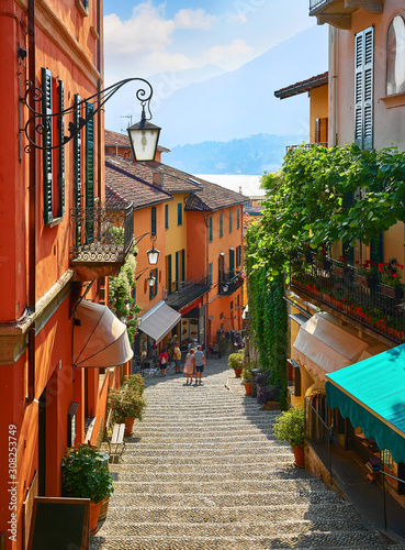 Fototapeta Bellagio village at lake Como near Milan Italy, region Lombardy. Famous street with paving stones stairs and cosy restaurants during sunrise with glowing lanterns and green plants on old houses walls. obraz