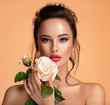 Beautiful white girl with rose.  Stunning brunette girl with white flower. Closeup face of young beautiful woman with a healthy clean skin. Pretty woman with bright makeup