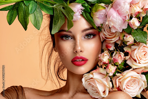 Obraz Beautiful white girl with flowers. Stunning brunette girl with big bouquet flowers of roses. Closeup face of young beautiful woman with a healthy clean skin. Pretty woman with bright makeup - fototapety do salonu