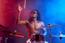 Portrait Of Showy African Drummer Man With Percussion Instruments Isolated Over Neon Smoky Background