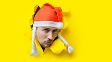 A Young Guy With A Beard And A Mustache With Duck Lips In A Santa Claus Or Snow Maiden Hat With White Pigtails Peeps Out Of A Torn Hole In Yellow Paper. The Concept Of Christmas, New Year. Copy Space.