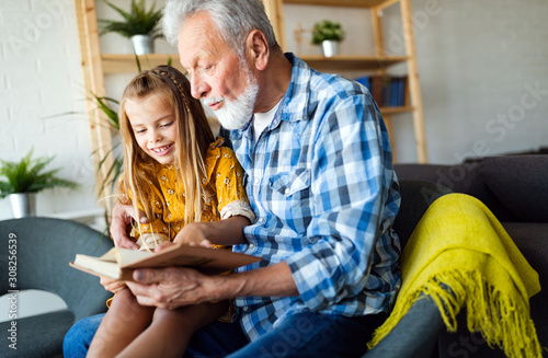 Fotomural Bearded grandfather and his grandchild are having fun reading a book together