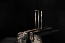 Image - 3 Silver Iron Nails Standing In Bench Vise Iluminated With Natural Light On Black And Dark Background. Heads Of Nails In Darkness.