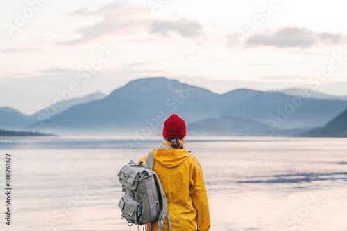 Obraz Alone traveler wearing yellow raincoat and backpack looking at fantastic fjord and mountain landscape. Lifestyle outdoor adventure, scandinavian wanderlust - fototapety do salonu