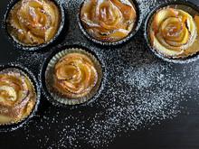 Rose Di Mele Con Pasta Sfoglia Spolverate Con Lo Zucchero A Velo Su Uno Sfondo Scuro. Vista Dallì'alto