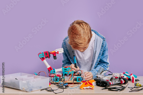 Fototapeta portrait of blond boy concerned with assembling robotics child boy holding robots, technique and trying to assemble them in one. robots and children concept obraz