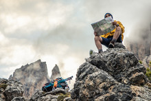 Young Man Hiker Sitting On Sto...