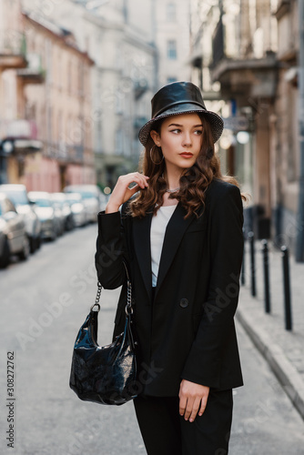 Outdoor fashion portrait of young elegant confident model, woman wearing trendy faux leather bucket hat, black suit, holding stylish hobo bag, handbag, posing in street of European city Wall mural