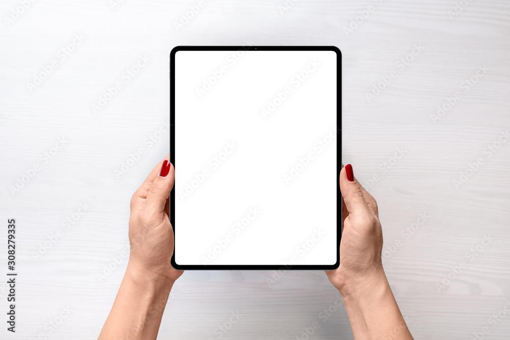Fototapeta Tablet mockup. Girl holding tablet in vertical position abowe white desk. Flat lay, top view