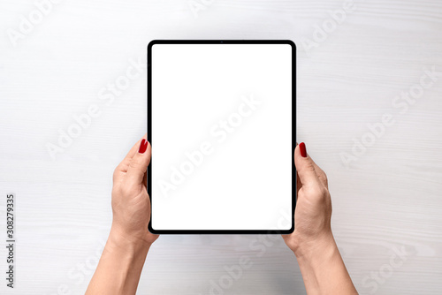 Obraz Tablet mockup. Girl holding tablet in vertical position abowe white desk. Flat lay, top view - fototapety do salonu