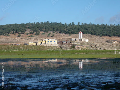 Fototapeta Small wayside mosque in rural countryside reflected in lake - Morocco
