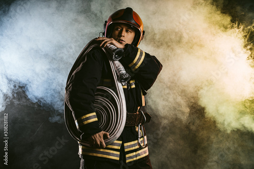 Canvas Print handsome fireman in helmet stand isolated in smoky space, wearing uniform