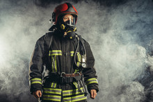 Brave Extinguisher Or Fireman Dressed In Dark Protective Suit Uniform, With Helmet On Head, Using Ropes, Hammer And Other Special Equipment At Work
