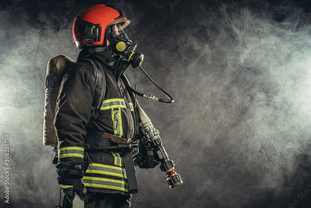 Fototapeta strong firefighter in protective suit and helmet use special equipment for preventing fire and save people and animals from fire