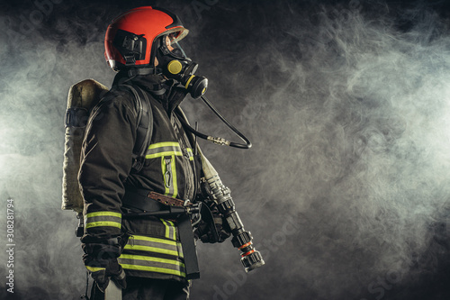 Obraz na płótnie strong firefighter in protective suit and helmet use special equipment for preve