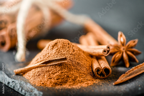Foto Heap of cinnamon powder on dark stone table
