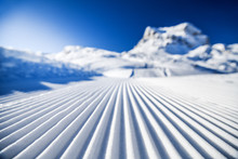 New Groomed Ski Piste Or Slope. Lines In Snow With Sunny Mountains Background. Winter Skis Concept.