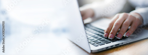 Business woman working on modern computer banner or panorama. Person buying online at internet. Laptop focused on keyboard detail with blur hand. copy space for text.