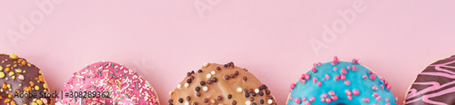 Halfs of different types colorful donats decorated sprinkles and icing on a past фототапет