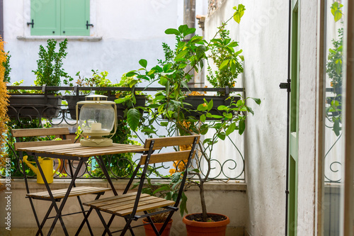 Carta da parati An Italian balcony with green potted plants and garden furniture