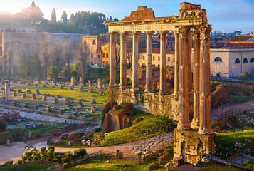 Fototapeta Vintage Roman Forum in Rome, Italy. Antique structures with columns. Wrecks of ancient italian roman town. Sunrise above famous architectural landmark.